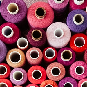A set of threads of different colors on the pink background. Many threads for sewing and needlework are different in color and size. Multicolored palette of threads.