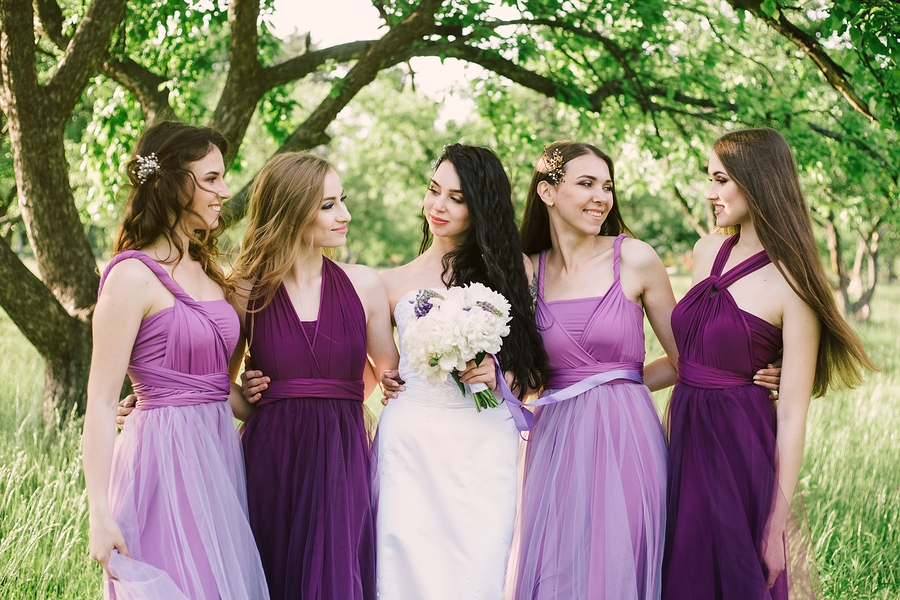 Emotional bride and bridesmaids are talking and smiling.