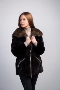 Young dark-haired woman in black fur coat